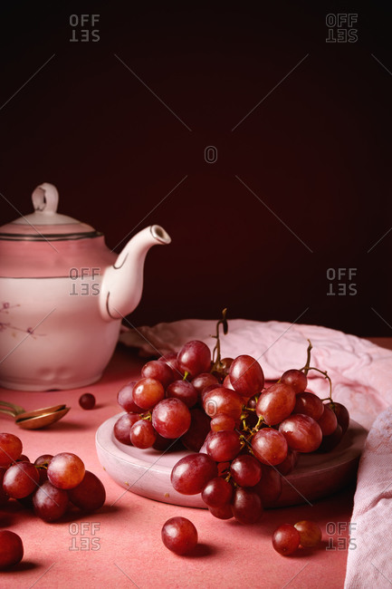 Still life composition with white porcelain teapot and tea spoon placed on round table near plate with ripe red grapes against black background