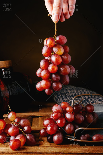 Crop unrecognizable person taking bunch of fresh juicy red grapes from tray placed on wooden table against black background