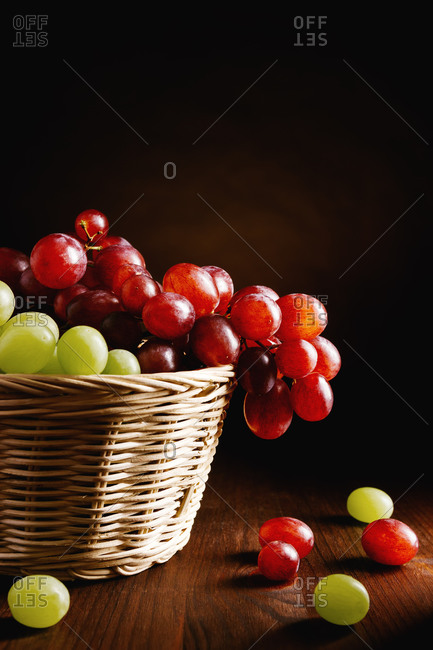 Wicker basket filled with appetizing fresh green and red grapes placed on wooden table against black background