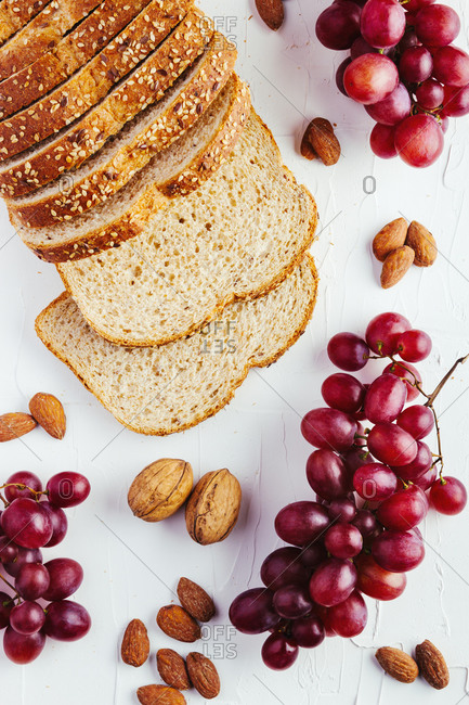 Top view composition with sliced bread and red and green grapes arranged on white table with walnuts and almonds