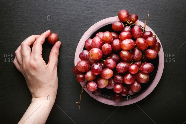 Top view of crop hand holding red grape near bowl of ripe red grapes placed on black surface