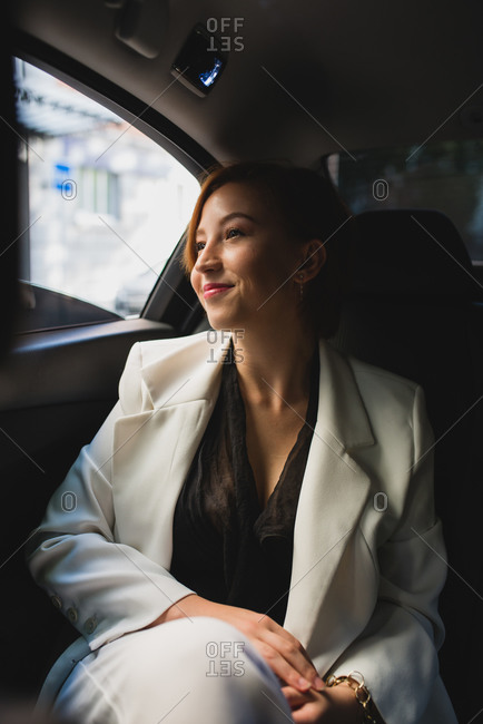 Content businesswoman in elegant suit sitting on passenger seat in taxi and commuting to work while looking out of window
