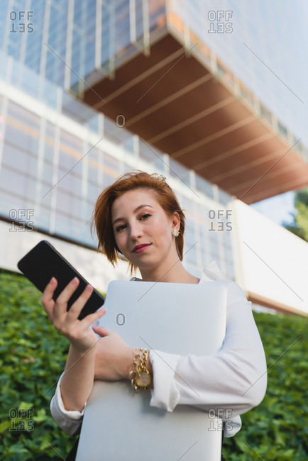 Low angle of determined female executive manager wearing medical mask standing with laptop and smartphone on street and looking away
