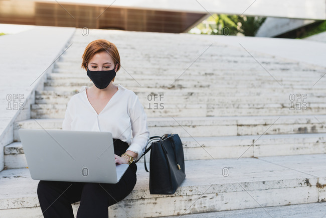 Businesswoman in formal wear and protective mask sitting on stone steps in city and working on netbook during COVID 19 epidemic