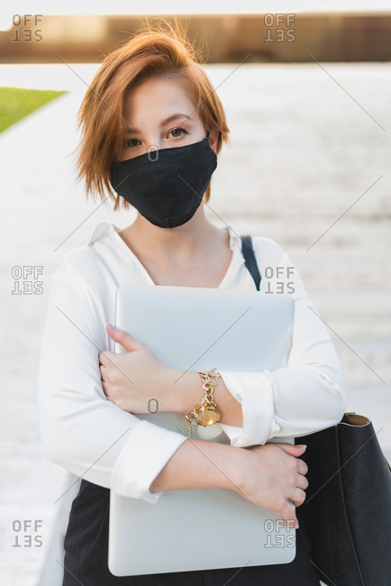 Determined female executive manager wearing medical mask standing with laptop on street and looking at camera