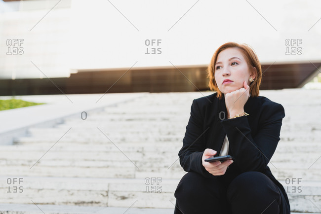Thoughtful female manager in elegant suit sitting stairs in city and on cellphone while looking away