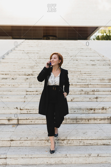 Content female manager in elegant suit walking down the stairs in city and discussing work issues on cellphone while looking away
