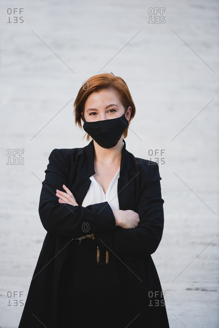 Determined female entrepreneur wearing elegant suit and protective mask standing with crossed arms near building and looking at camera