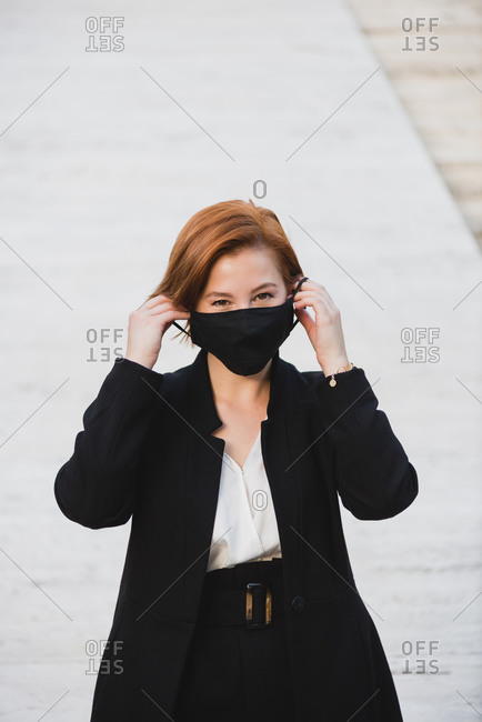 Determined female entrepreneur wearing elegant suit and protective mask standing near building and looking at camera