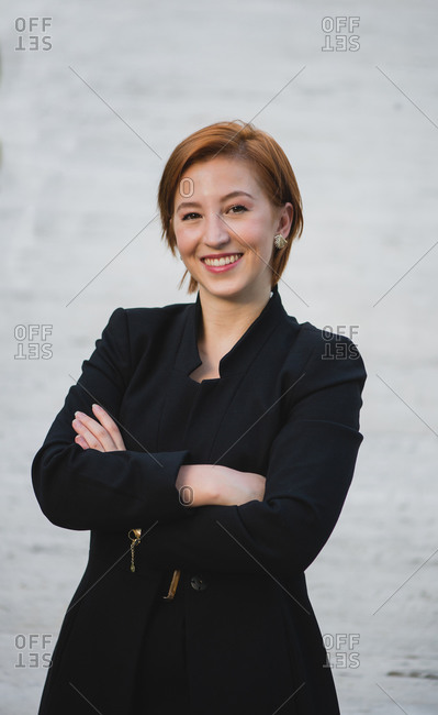 Positive female entrepreneur wearing classy suit standing with crossed arms near stone building in city and looking at camera