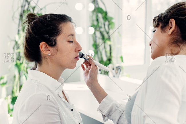 Side view of female makeup artist applying powder on face of model sitting in beauty salon with closed eyes