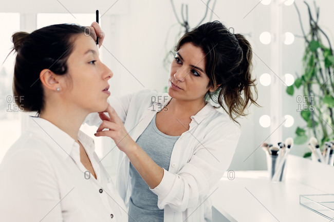 Makeup artist applying eyeshadow on face of female model in contemporary beauty club