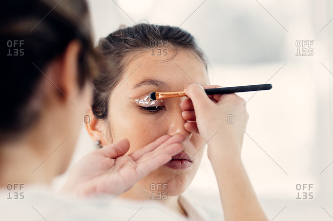 Back view of unrecognizable female visagiste applying glowing eyeshadows while doing makeup on face of model in beauty salon