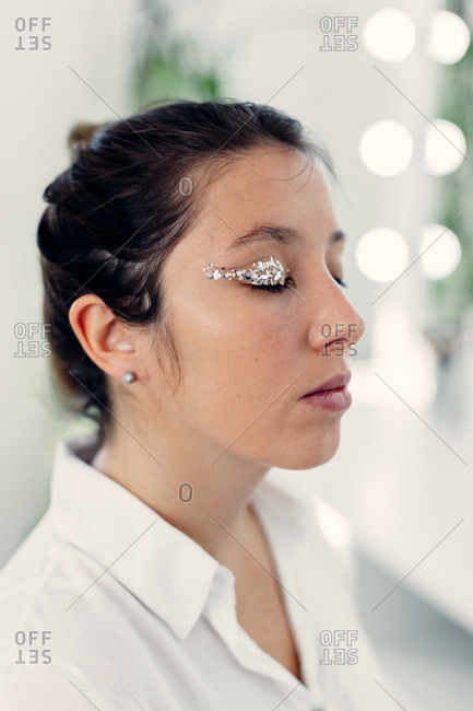 Side view of charming female model with glowing eyeshadows sitting with closed eyes in bright beauty studio