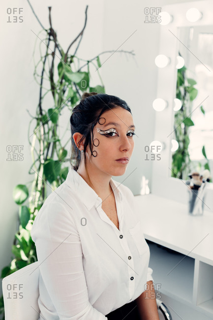 Unemotional female model with creative hairstyle and glowing makeup sitting in modern beauty salon and looking at camera