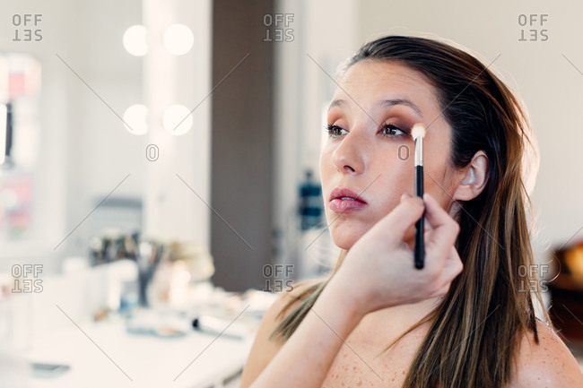 Unrecognizable makeup artist applying eyeshadow on face of female model in contemporary beauty club
