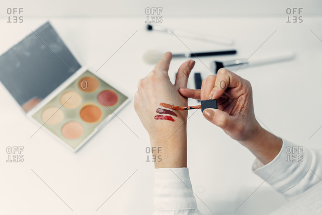 From above of faceless female makeup artist applying liquid lipstick on hand while working in modern beauty salon