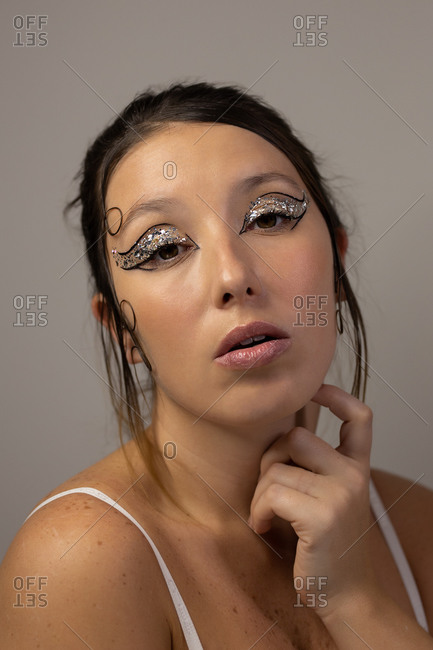 Flawless female with shiny eyeshadow and perfect skin looking at camera in studio on gray background