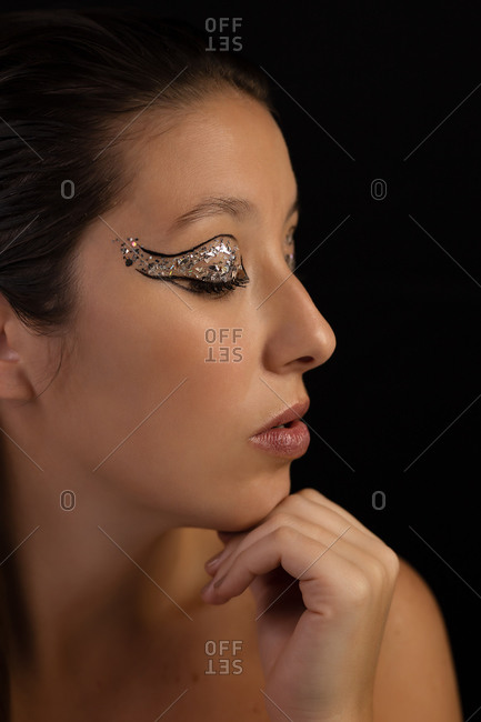 Flawless female with shiny eyeshadow and perfect skin looking down in studio on gray background