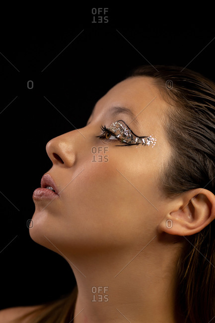 Flawless female with shiny eyeshadow and perfect skin looking up in studio on gray background