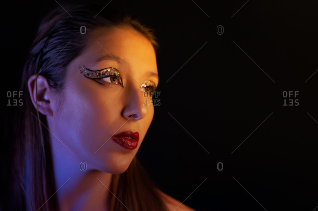 Flawless female with shiny eyeshadow and perfect skin looking away in studio on gray background