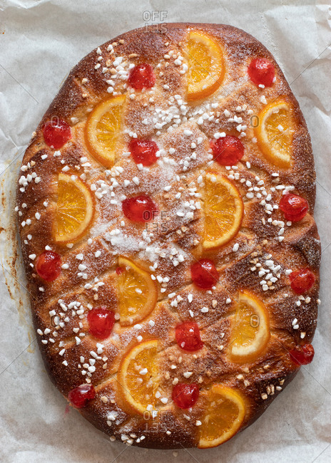 From above traditional Catalonia coca de San Juan cake decorated with orange and cheery
