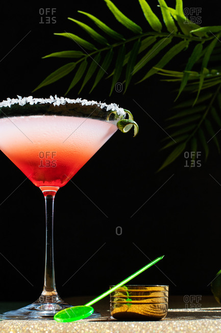 Tropical Margarita Cocktail with Grenadine placed on glittery table with plant leaves on black background