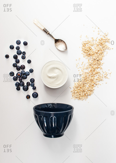 From above ingredients oats, fresh yogurt and blueberries to make healthy breakfast on white table