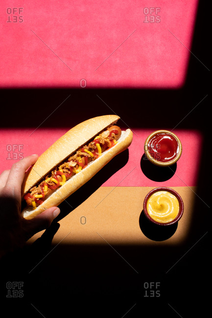 From above frankfurt hot dog with mustard and ketchup served on small bowls on colorful background
