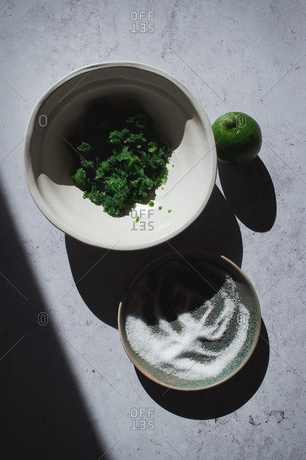 From above basil sugar served on small bowls near lime and fresh yogurt on rustic table with shadows lights