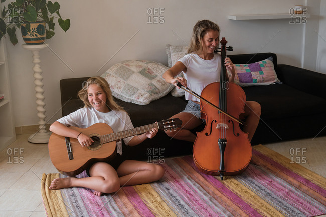 Blonde woman and girl smiling as they play a guitar and cello in a dining room of a house