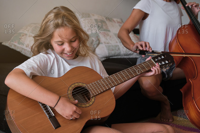 Caucasian blonde girl smiling while is playing a guitar sitting on the floor of a house with a woman playing cello next to her
