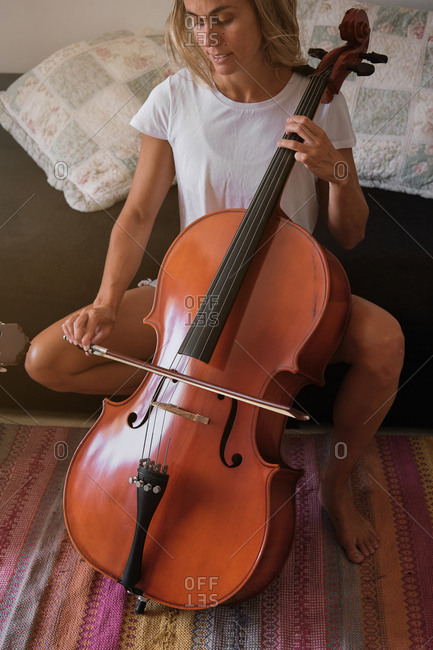 Vertical photo of a blonde woman playing the cello sitting on the sofa of a house in summer clothes and barefoot