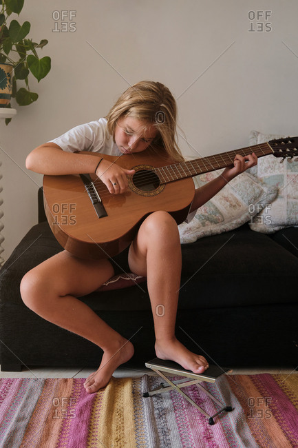 Vertical photo of a girl sitting on a sofa playing the guitar with a concentrated expression with her foot leaning on a foot rest