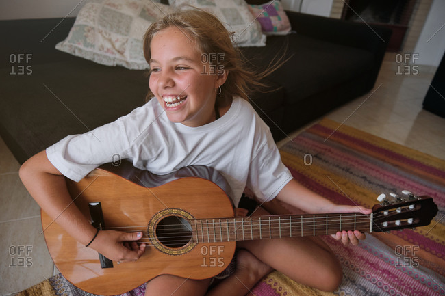 Blonde girl sitting on the floor of a house playing a guitar while is singing with happy expression and looking aside