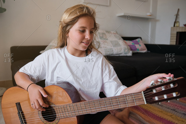 Blonde caucasian girl sitting on the floor of a house while tuning a wooden guitar