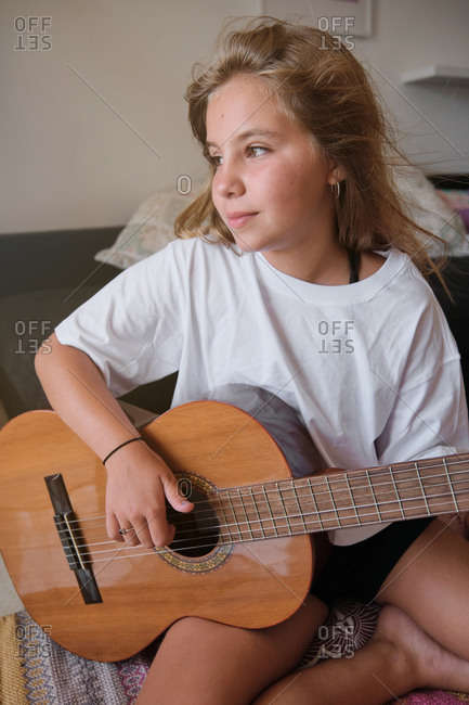 Vertical photo of a blonde girl looking to a side with distracted expression while playing a guitar in a room of a house with a sofa