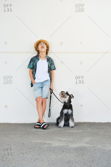 Vertical photo of a child with curly hair, straw hat and summer clothes leaning against a wall while is shouting with a dog on a leash