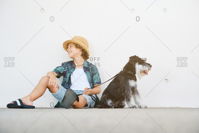 Child with curly hair, straw hat and summer clothes sitting on the floor in front of a wall holding a dog on a leash and looking aside