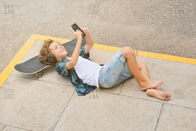 Vertical photo of a boy with printed shirt lying on the floor with his head on a skateboard listening to music on his mobile while is smiling