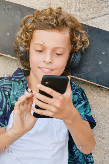 Vertical photo of the portrait of a boy with printed shirt lying on the floor with his head on a skateboard singing and listening to music while using his mobile