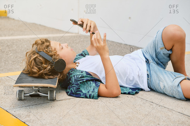 Boy in summer clothes lying on the floor with his head on a skateboard listening to music while looking his mobile