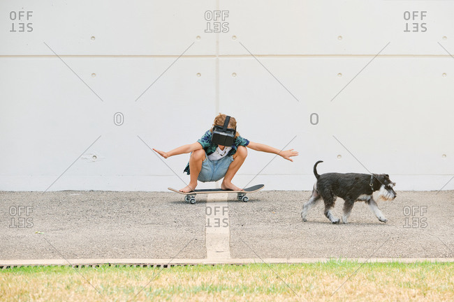Boy in summer clothes skating on skateboard wearing virtual reality glasses and gesturing with the arms raised on the street with a dog next to him