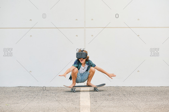 Boy in summer clothes skating on skateboard wearing virtual reality glasses and gesturing with the arms raised on the street
