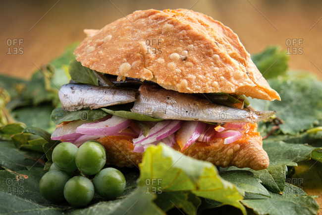 Small harvest sandwich with sardines, meat and different vegetables on top of a grapevine leaf. Gastronomy of Canary Islands