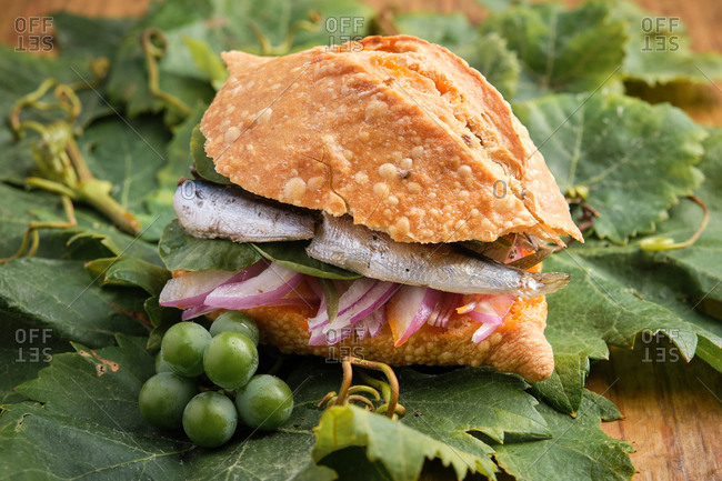 Traditional harvest sandwich with sardines, meat and different vegetables on top of a grapevine leaf. Gastronomy of Canary Islands