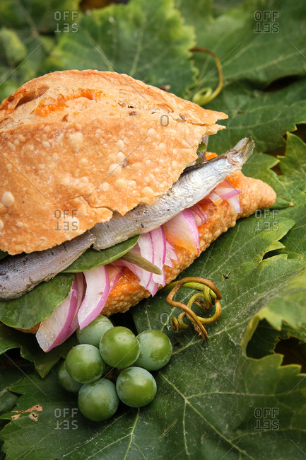 Vertical photo of the traditional harvest sandwich with sardines, meat and different vegetables on top of a grapevine leaf. Gastronomy of Canary Islands