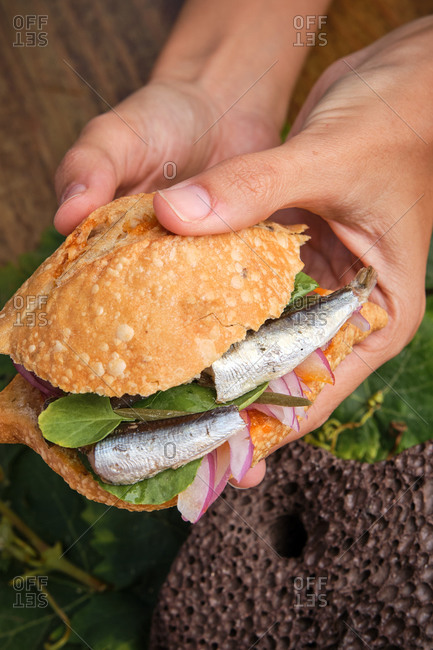 Vertical photo of a hands grabbing a traditional harvest sandwich with sardines, meat and different vegetables. Gastronomy of Canary Islands