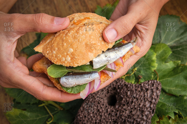 Photo of a hands grabbing a traditional harvest sandwich with sardines, meat and different vegetables. Gastronomy of Canary Islands