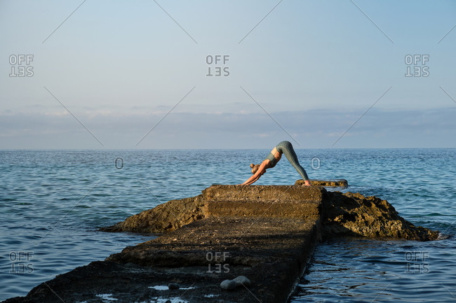 Side view of distant unrecognizable woman standing in Downward Facing Dog position while practicing yoga on rocky pier at seaside